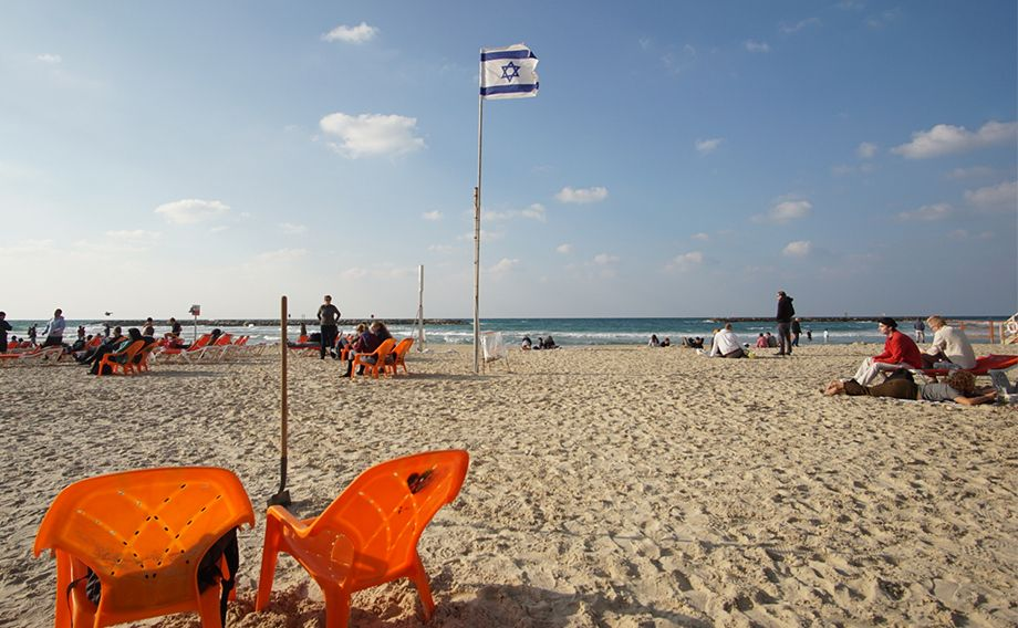 Image of a beach with the Israeli flag as the focal point.