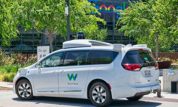 Image of a Waymo car in front of the Google sign