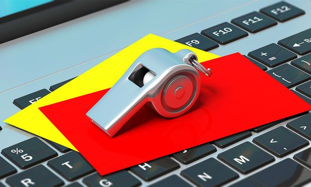 Image of a whistle paired with red and yellow cards, all on top of a laptop keyboard.