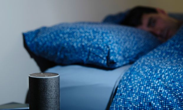 Image of Alexa sitting on a table next to a bed as someone sleeps.