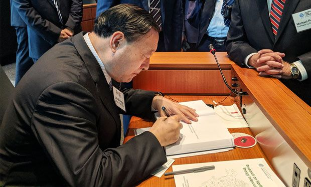 Image of Liu Zhenya signing a copy of his 2015 book, Global Energy Interconnection