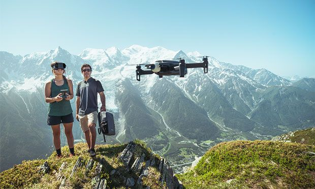 Image of two people flying the drone above a river.