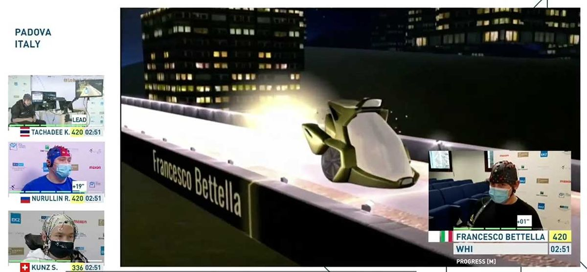 A computer generated car moves down an elevated road. An inset shows a masked man wearing a cap studded with electrodes.
