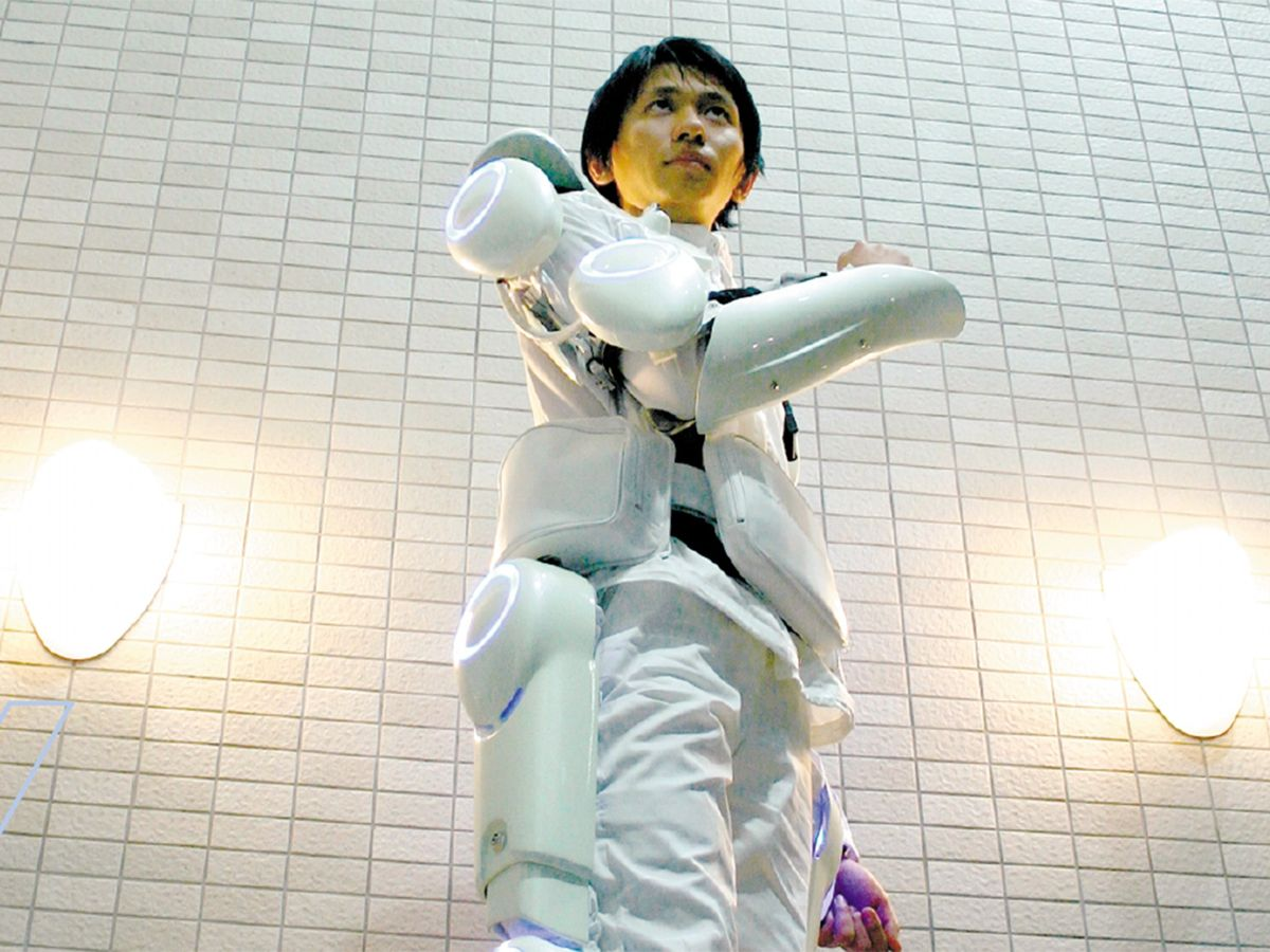 Photo of person wearing HAL-5, a powered robotic suit designed to help elderly and disabled people walk and carry things.
