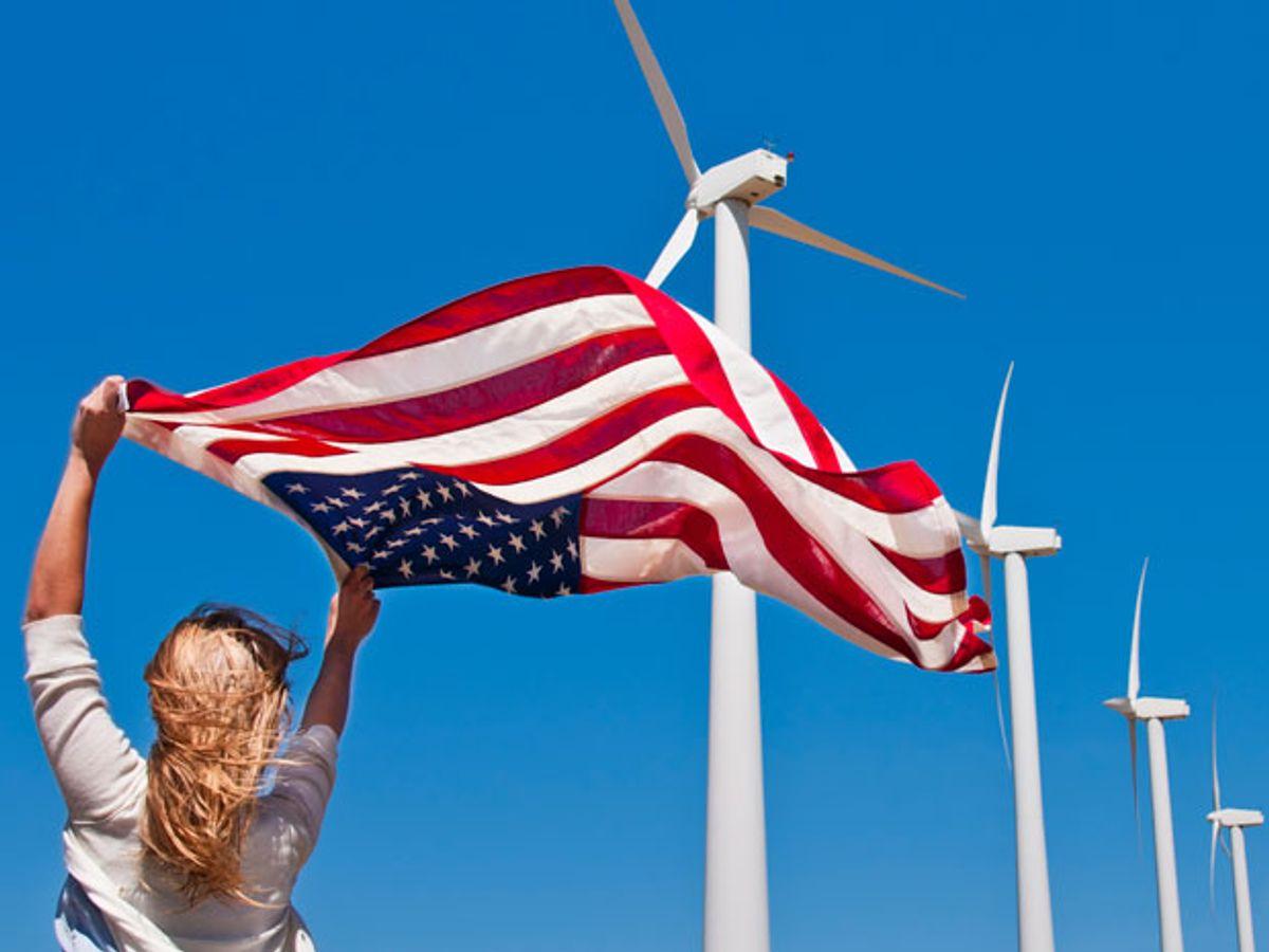 woman waves american flag near wind turbines