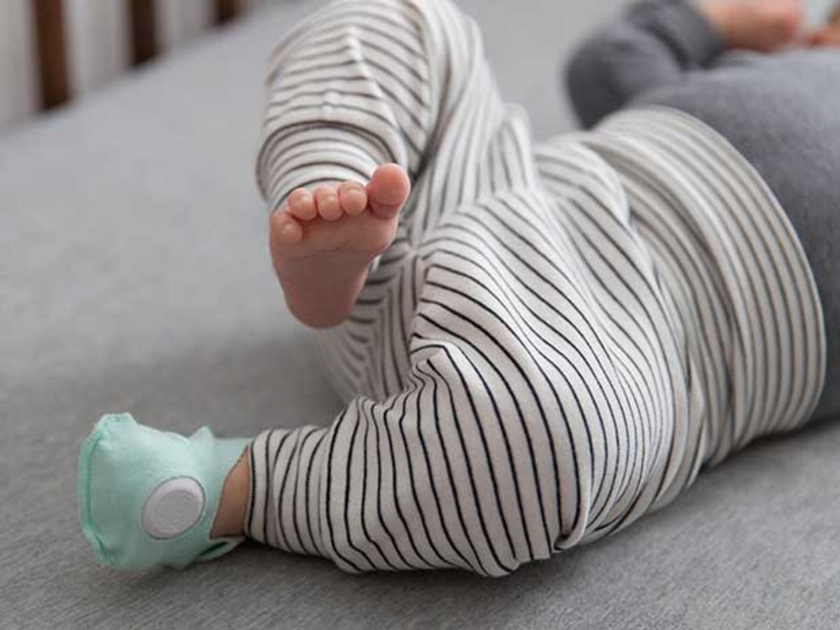 A baby lying in a crib is wearing one green cotton sock with embedded electronics.