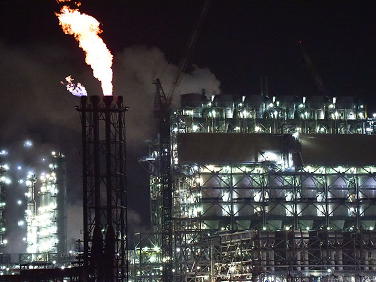 A power plant at night shrouded in steam