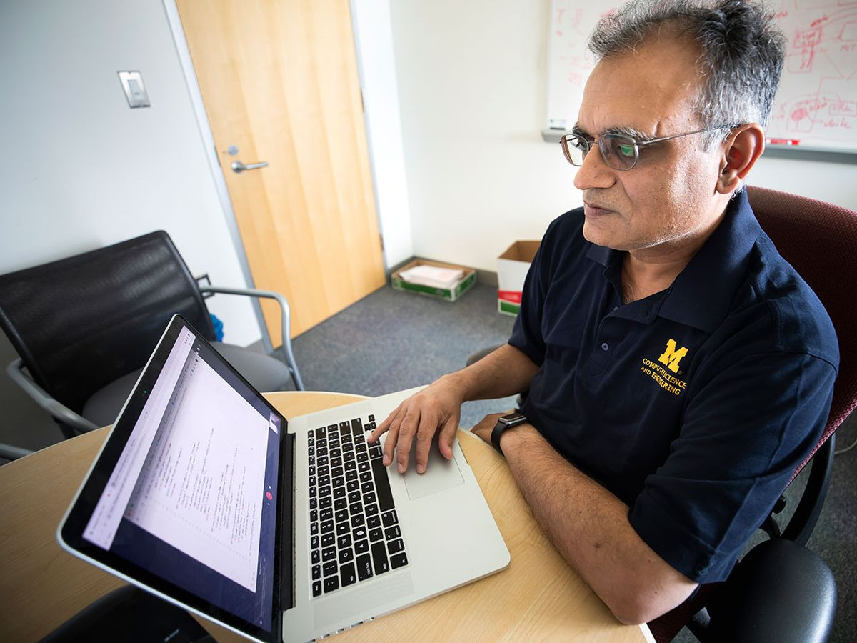 Atul Prakash, Professor of Electrical Engineering and Computer Science, works on code from a project giving Github users an infrastructure to report vulnerabilities.