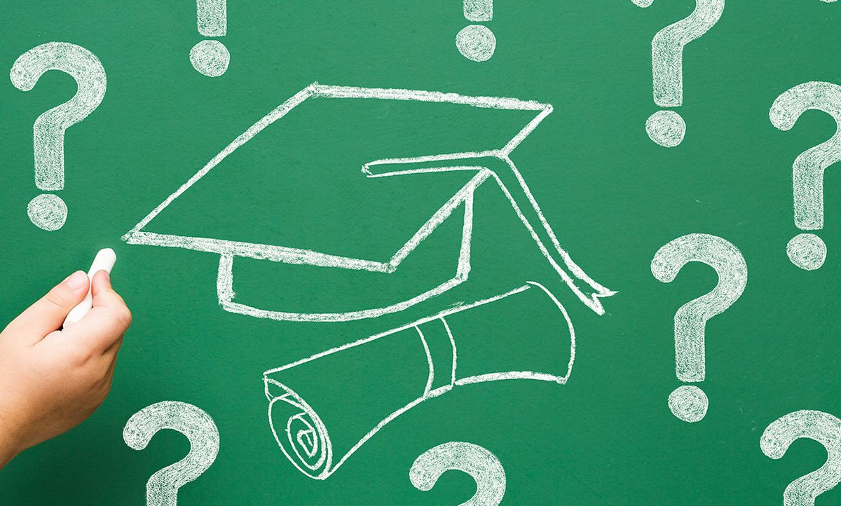 Hand holding chalk, writing on a chalkboard with a drawing of a graduation cap with question marks around it