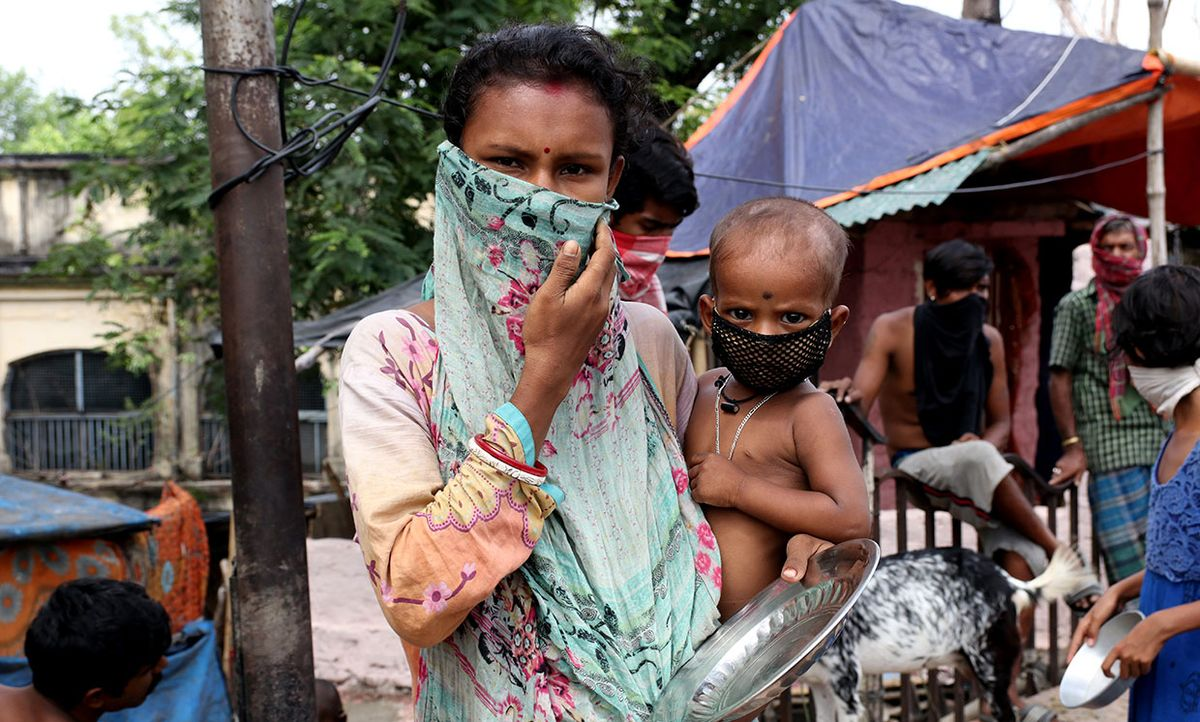 A mother and child queue to receive food during a government-imposed nationwide lockdown as a preventive measure against the COVID-19 coronavirus, at a slum in Kolkata on April 21, 2020. India.