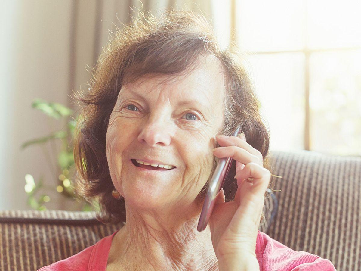 An elderly woman speaks on her phone