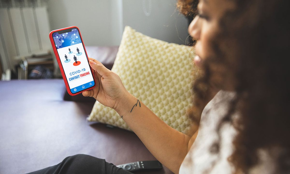 Woman checking a contact tracing app in her home.