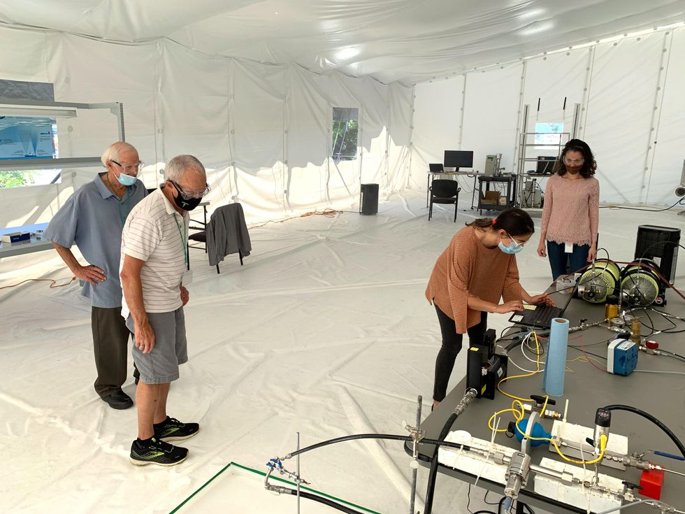 4 people in a large white text looking at equipment on a table
