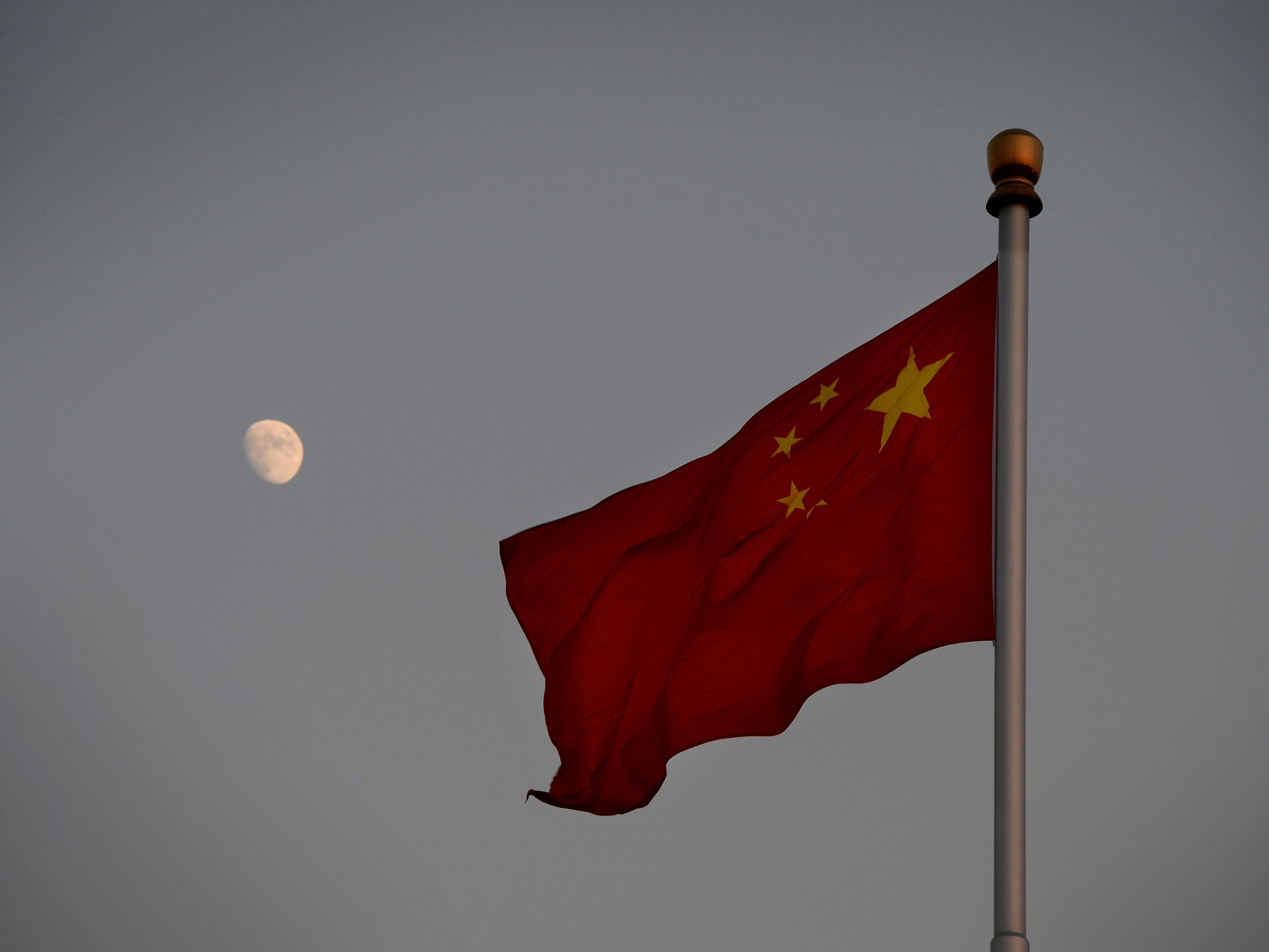 Image of the China national flash with the moon in the background.