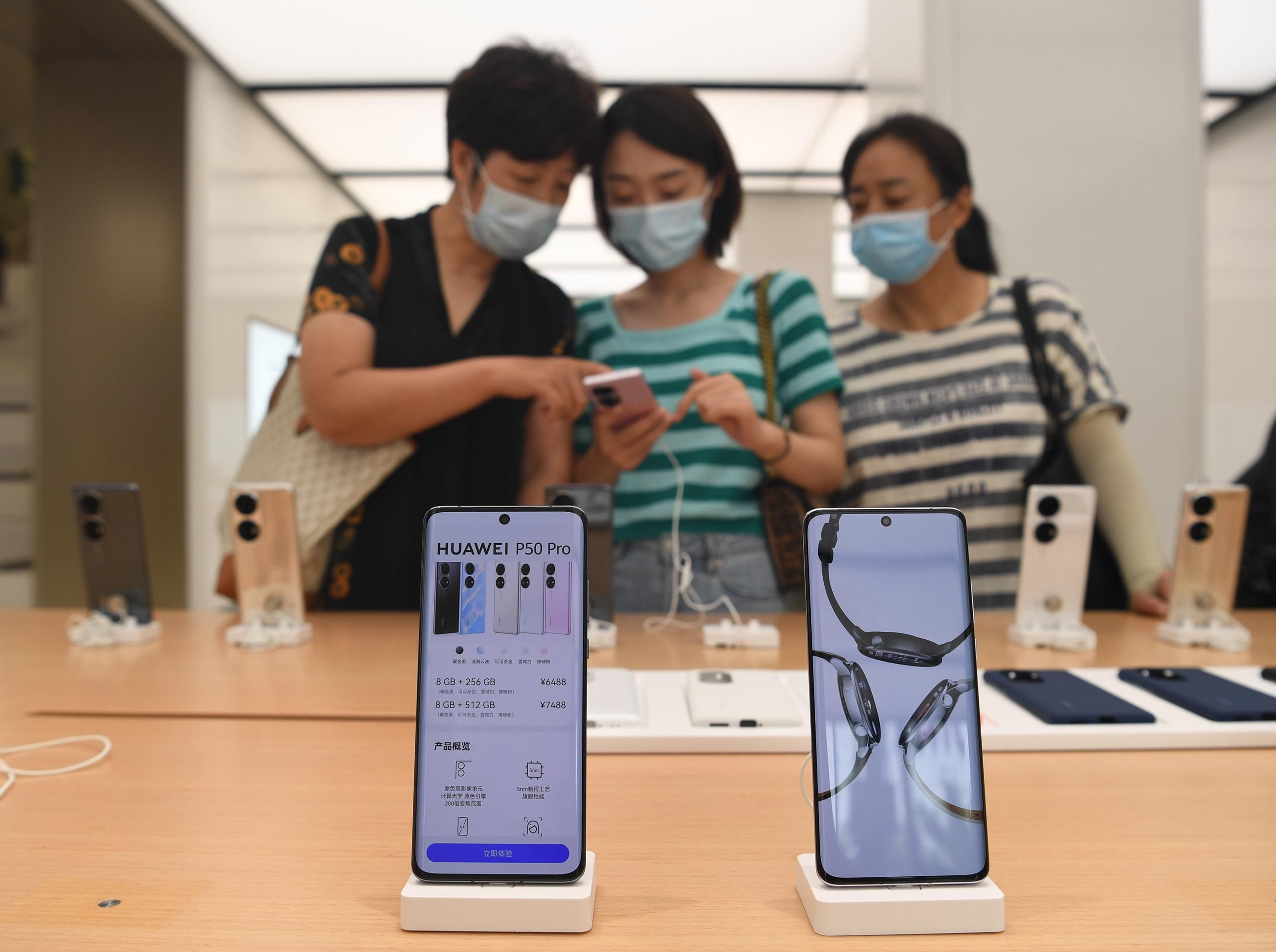 In the foreground, 2 rectangular phones sitting on white docks say Huawei P50 Pro. In the background, 3 women in masks look at phones on display.