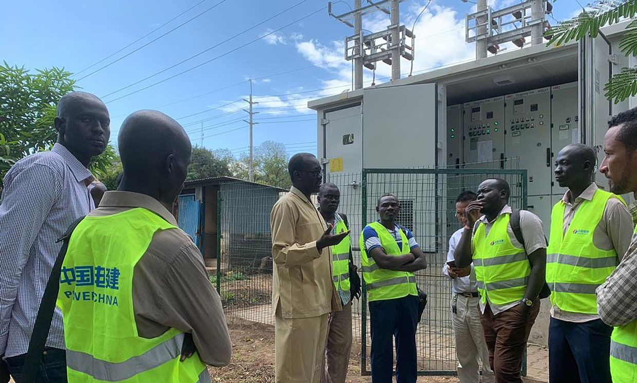 Jacob M. Deng, in a khaki suit, talks with utility workers during the commissioning of a substation in Juba, South Sudan.