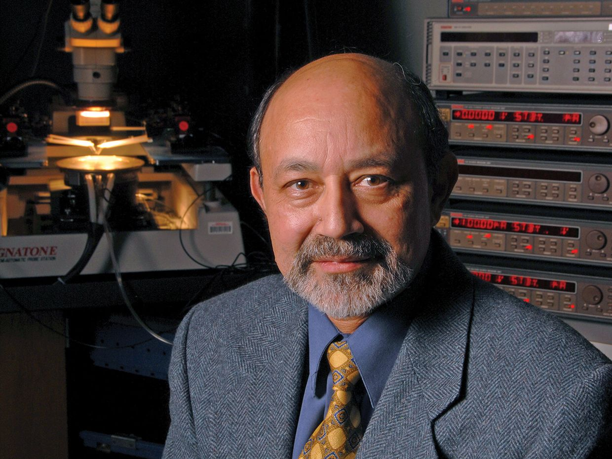 Jayant Baliga, a bald, bearded man with greying hair, sits in a laboratory in front of instruments and a microscope.