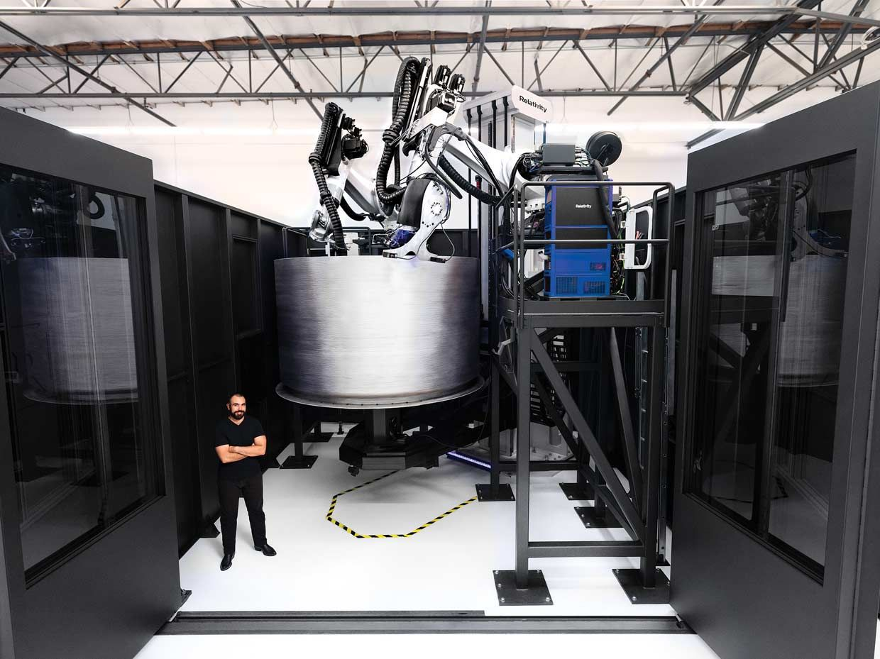 Jordan Noone, Relativity Space cofounder, stands in front of the company's newest 3D printer as it builds a fuel tank for the Terran 1 rocket.