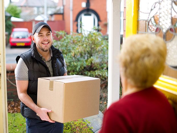 Lady opens a door for a delivery man with a package