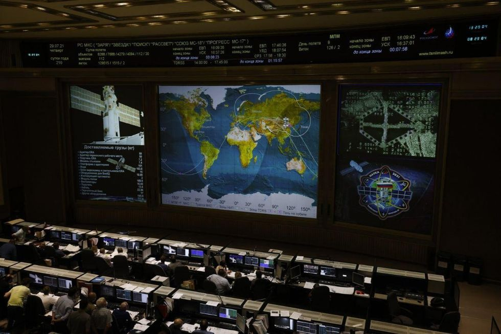 Large screens show a blue and green world map and close ups of space vehicles in front of rows of people in front of computer screens.