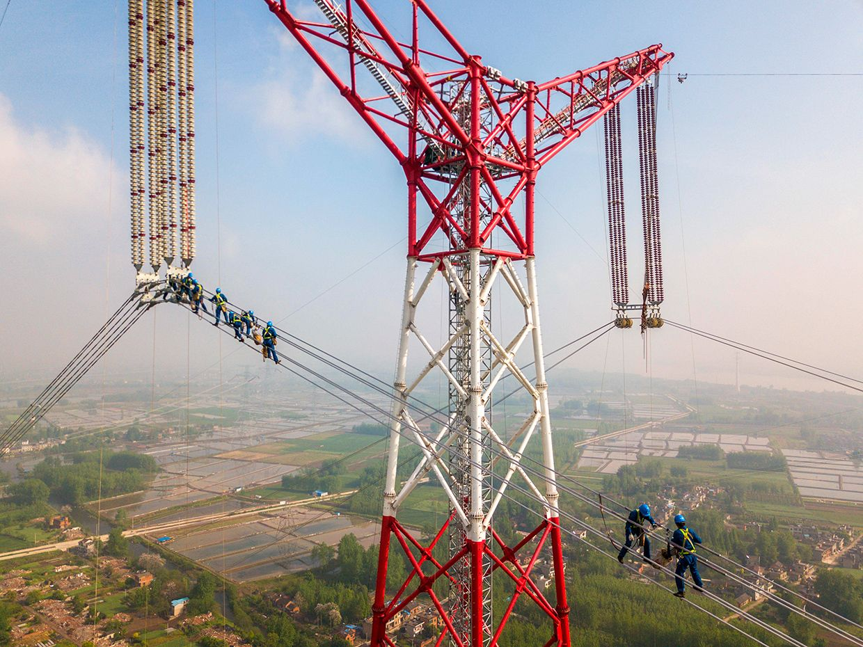 Men standing on high-tension wires.
