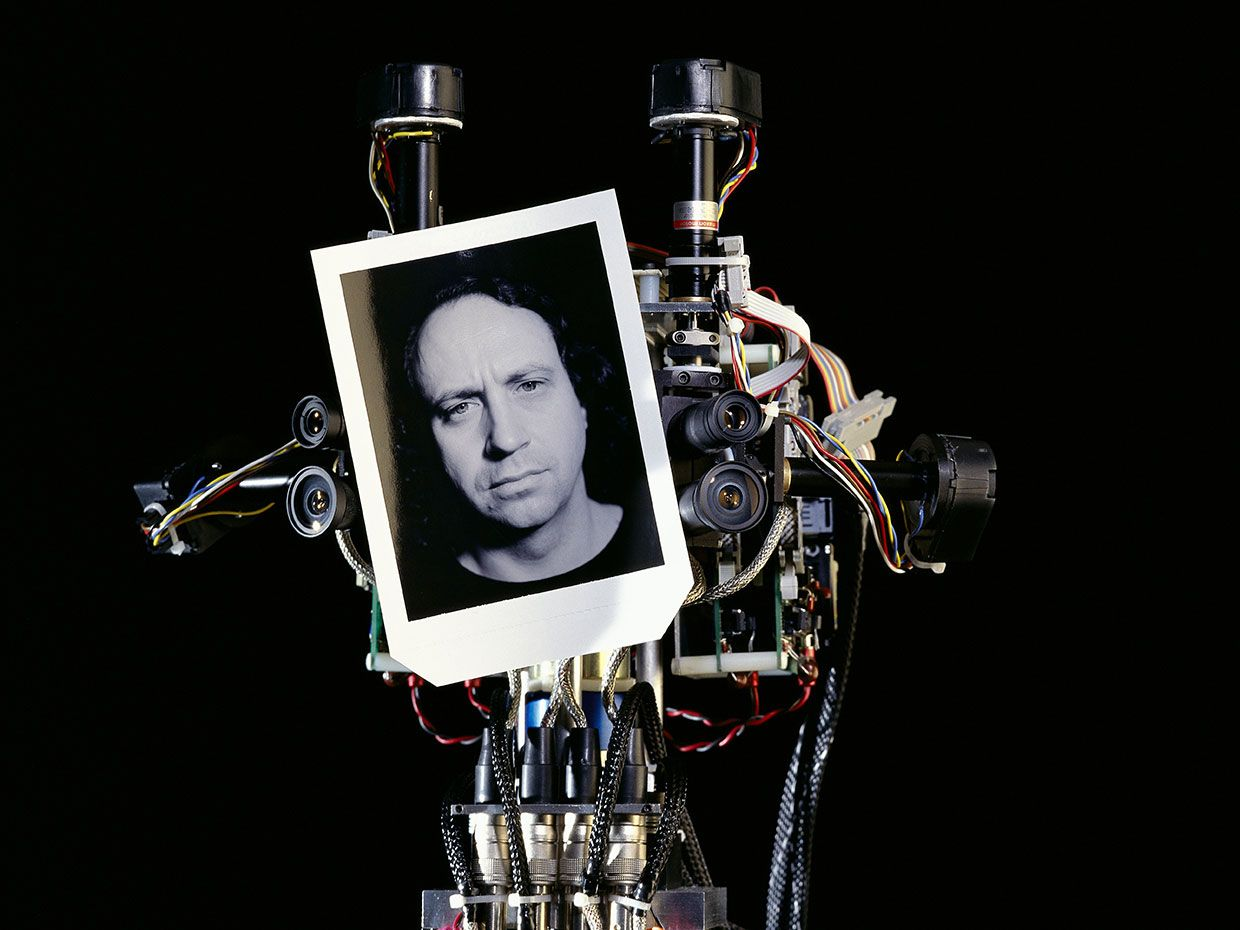 MIT humanoid robot Cog holding up a black and white portrait of Rodney Brooks