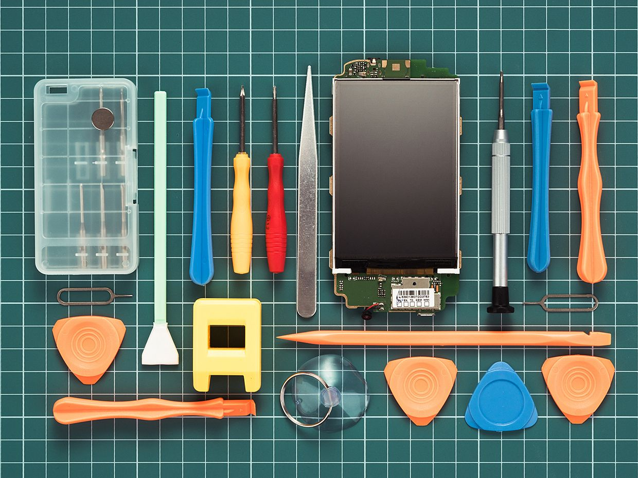 Mobile phone service tools on green grid workpad background.