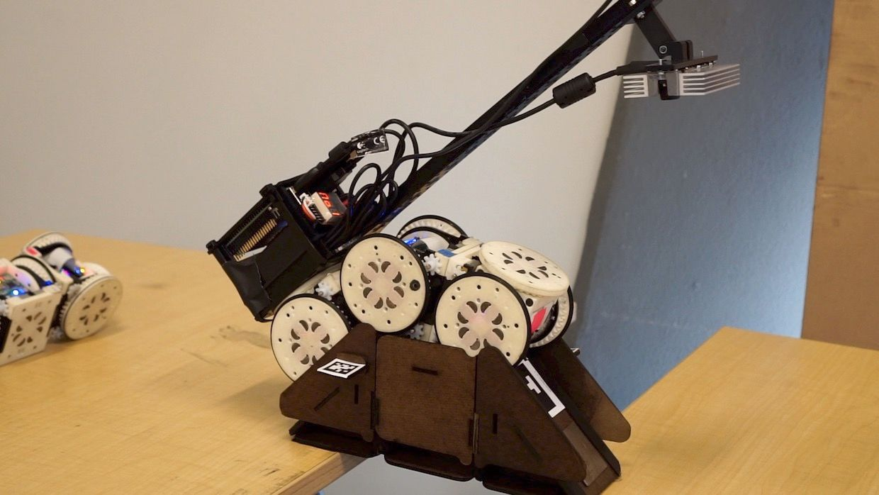 Modular robot completing tasks by deploying and crossing bridges and ramps made of building blocks