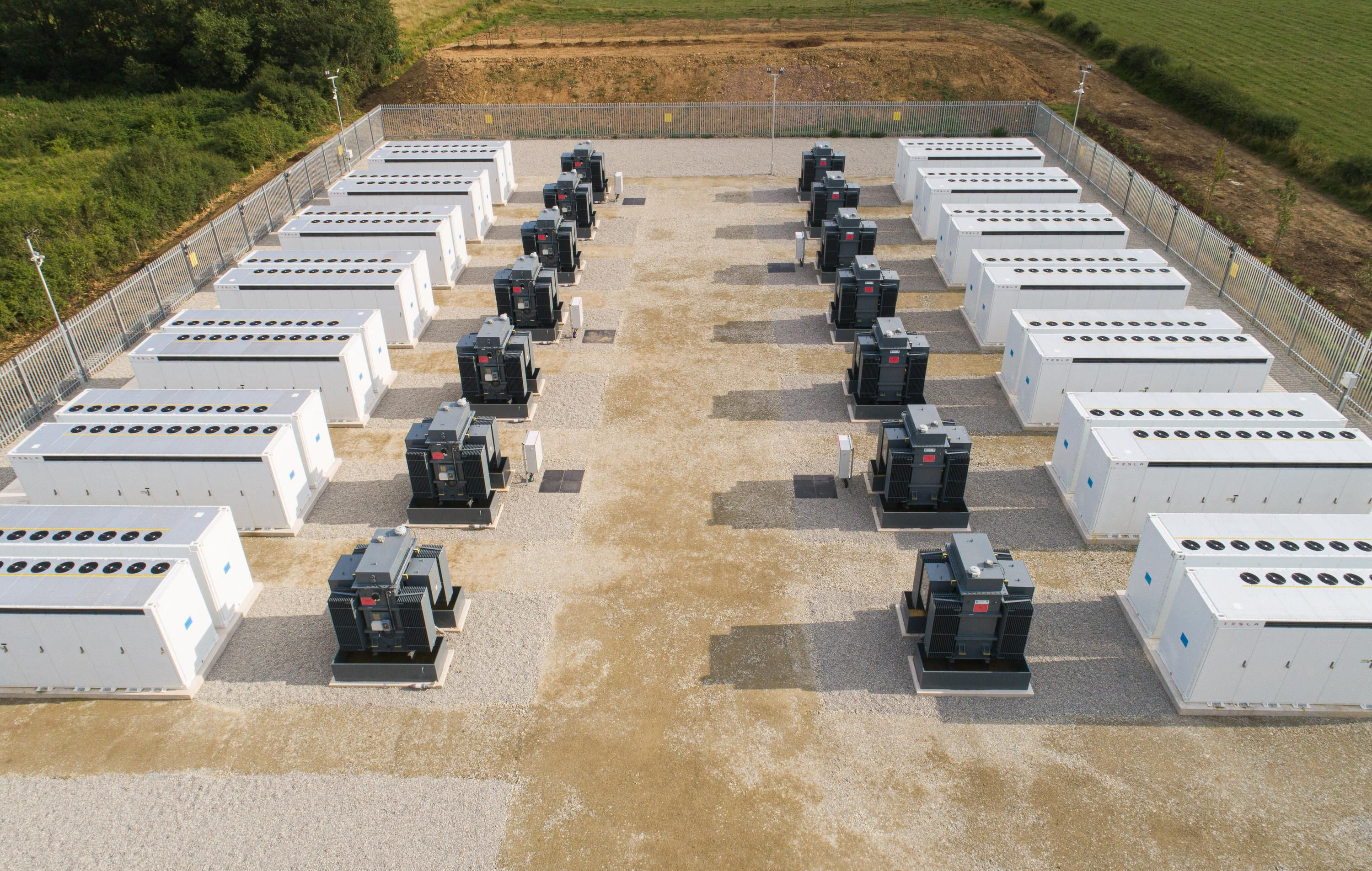 Overhead photo shows 7 large white containers and 7 black and gray large equipment boxes each on the left and right side in a grid.
