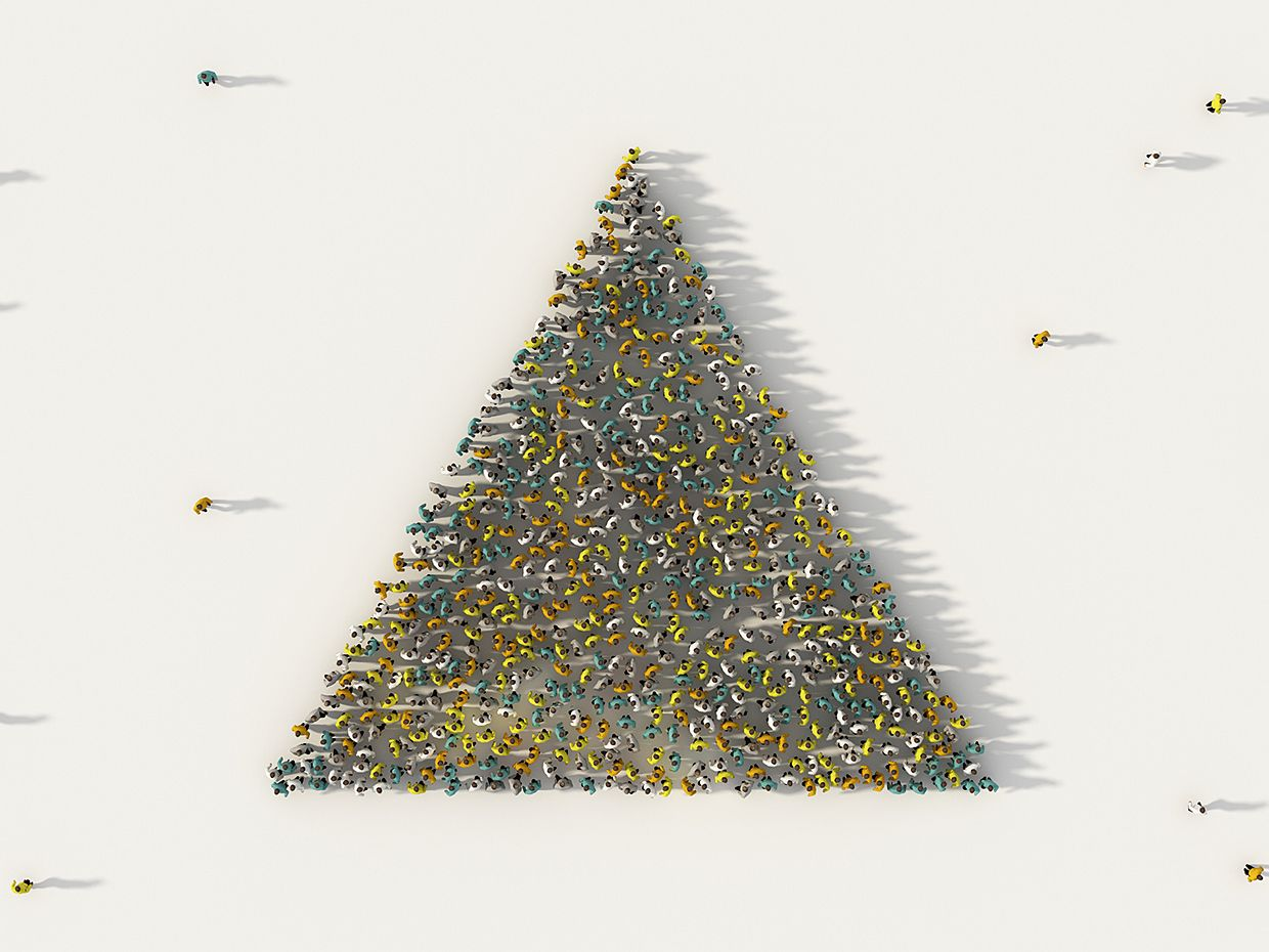 Overhead view of people standing to form pyramid shape.