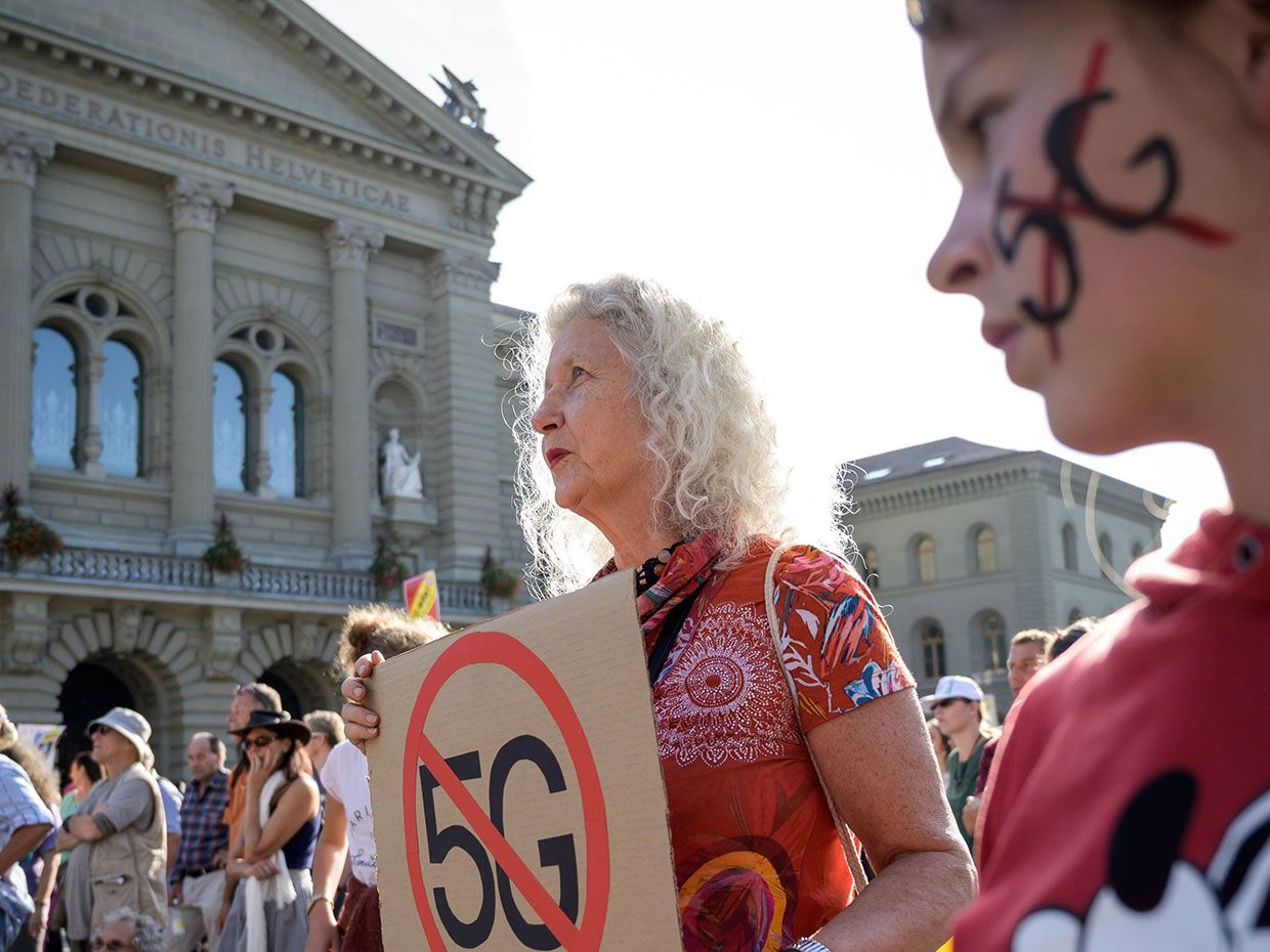 People take part in a nationwide protest against the 5G technology and 5G-compatible antenna deployment on 21 September in front of the Swiss House of Parliament in Bern.
