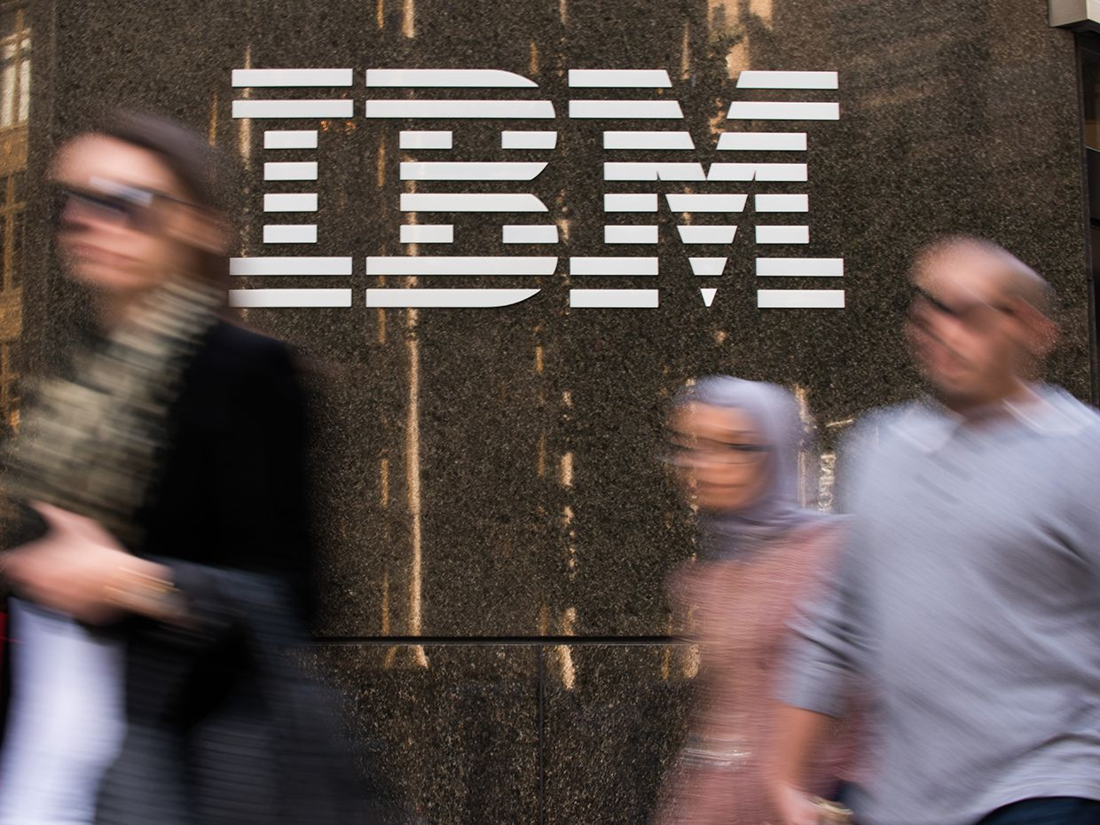 People walk in a blur past an IBM sign