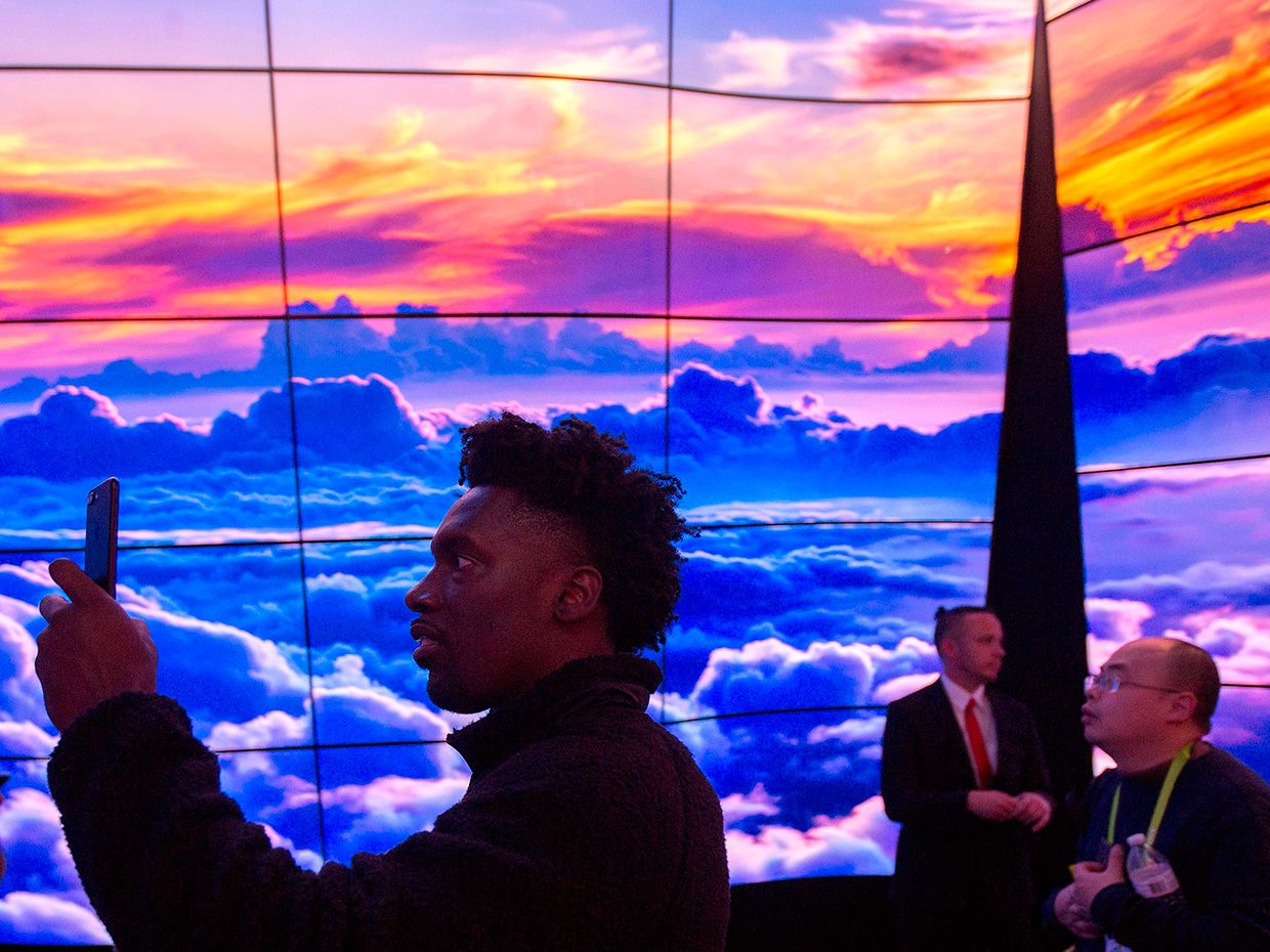 People walk through a display of LG OLED televisions at CES in Las Vegas, Nevada, January 9, 2018.