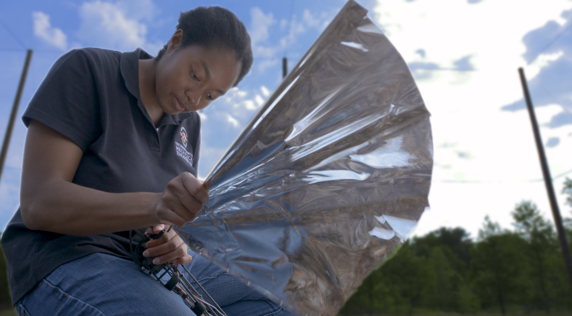 Ph.D. student Lena Johnson kneels to work on the fifth version of Robo Raven, a bird-inspired unmanned aerial vehicle with large silver wings.