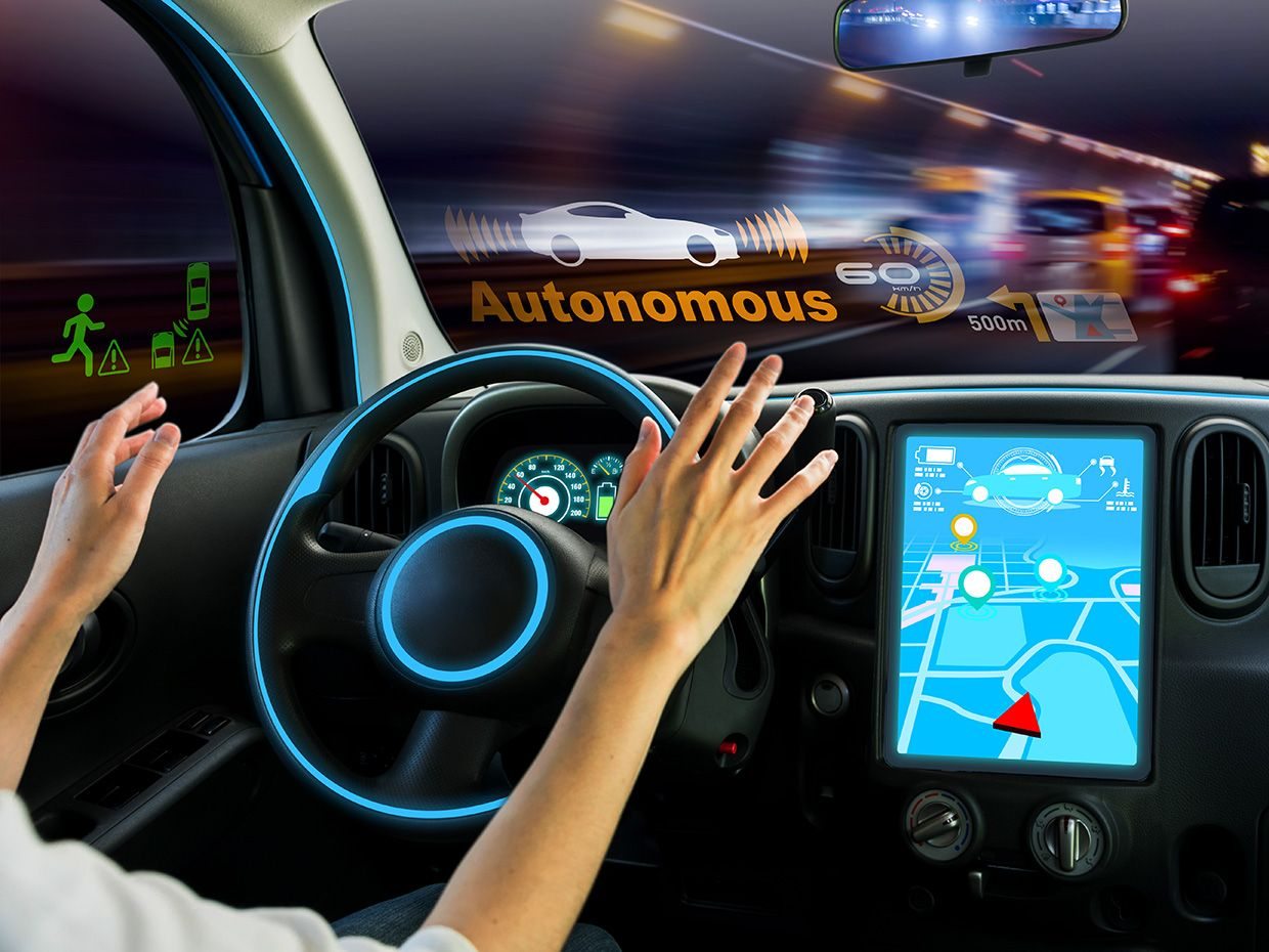 Photo-illustration of an autonomous car with the driver about to engage with the wheel.