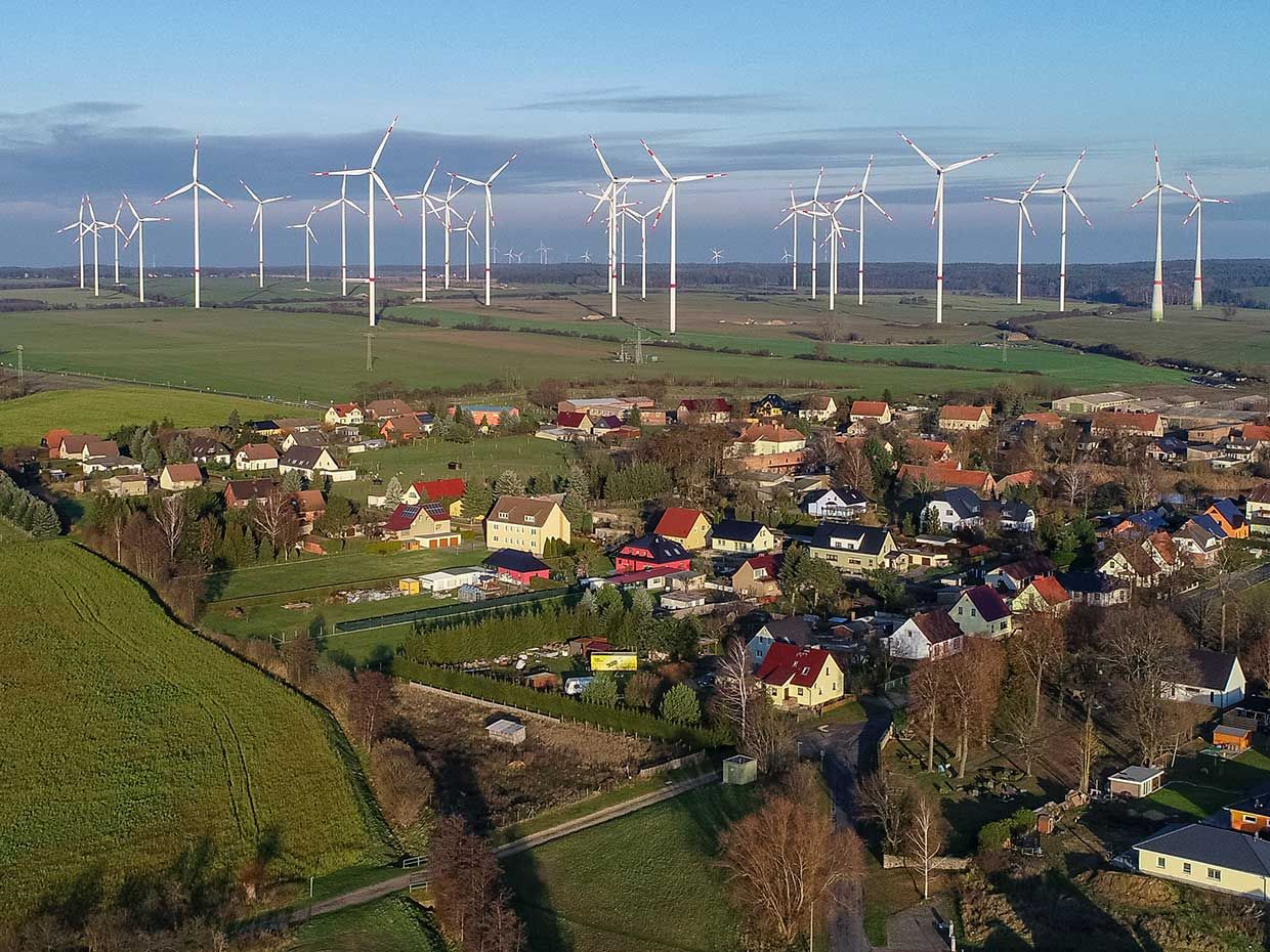 Photo of a village with windmills in the background.
