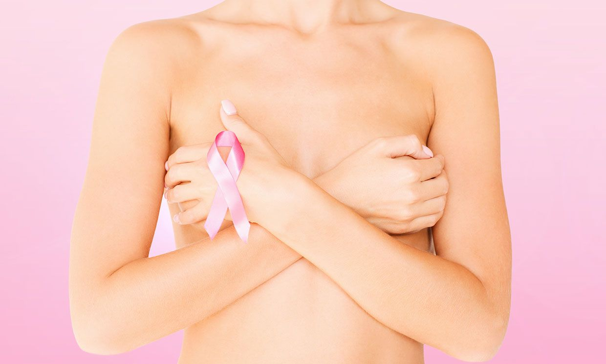 Photo of a woman with a breast cancer ribbon, covering her breasts.