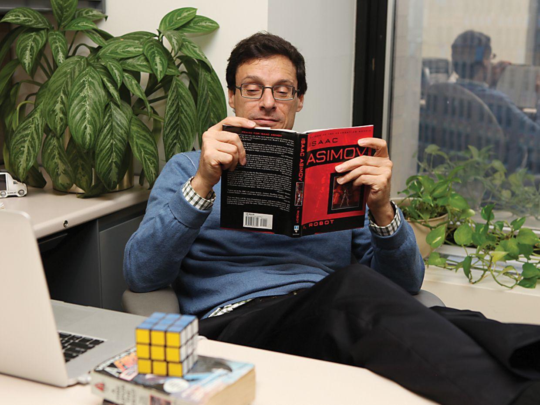 photo of man reading asimov at desk