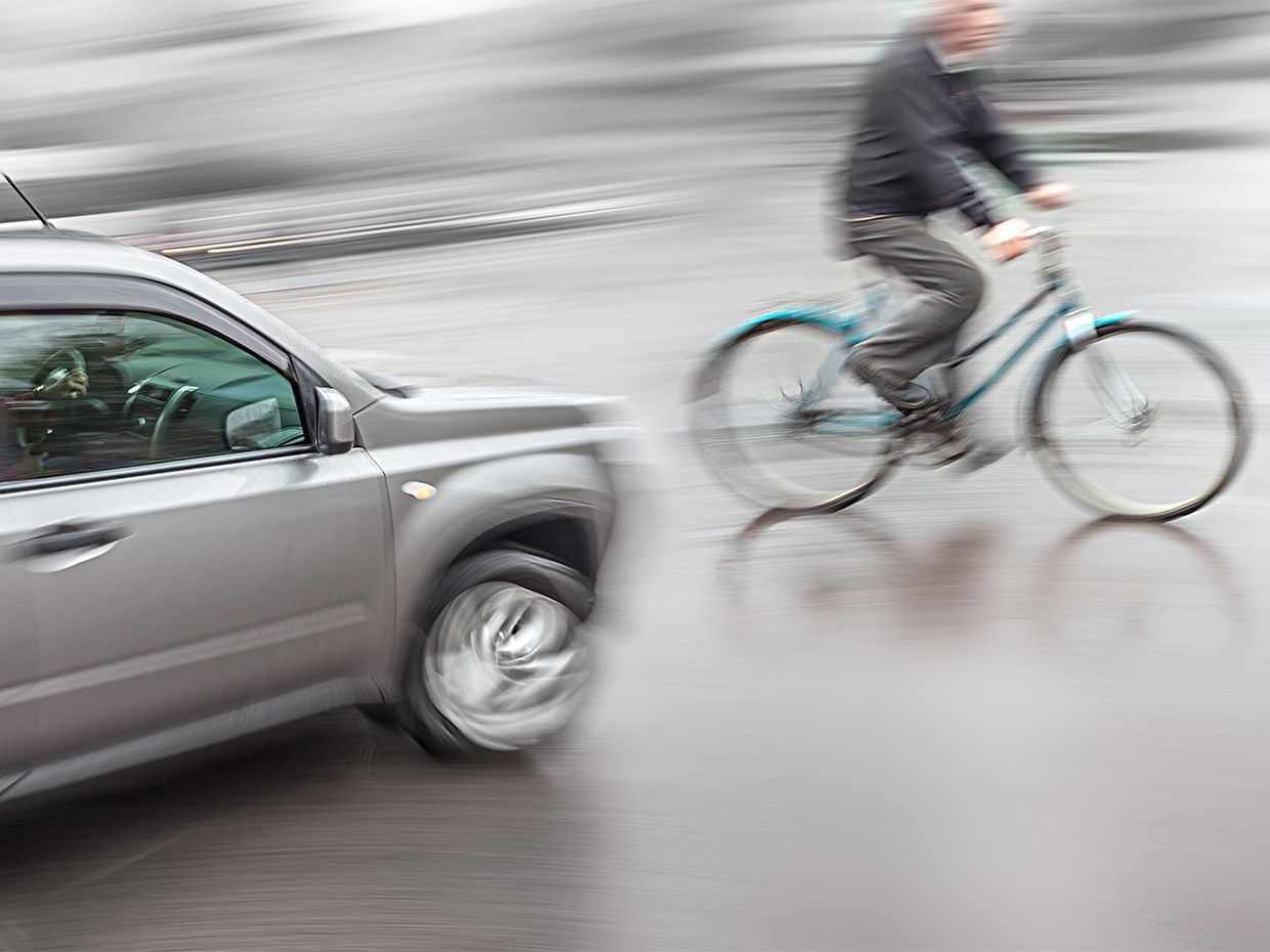 Photograph of a car and bicyclist nearly missing each other.