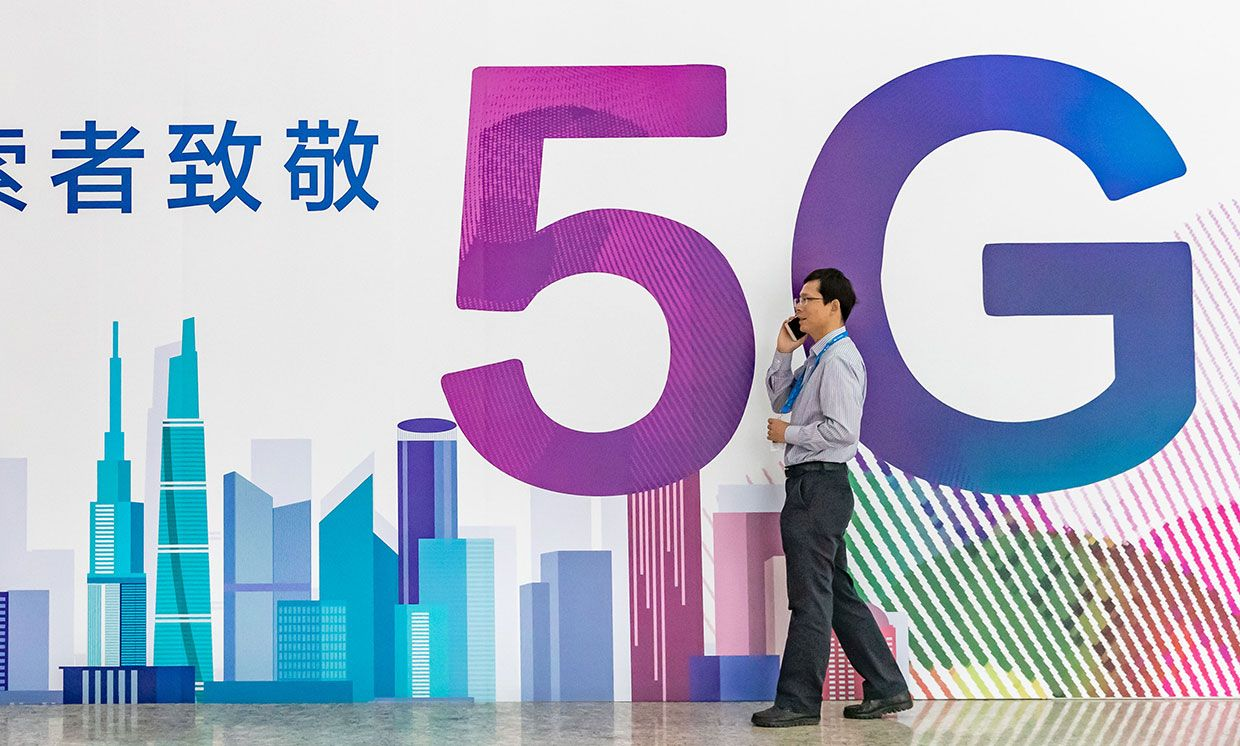 Photograph of a man in front of a 5G sign with Chinese characters on it.