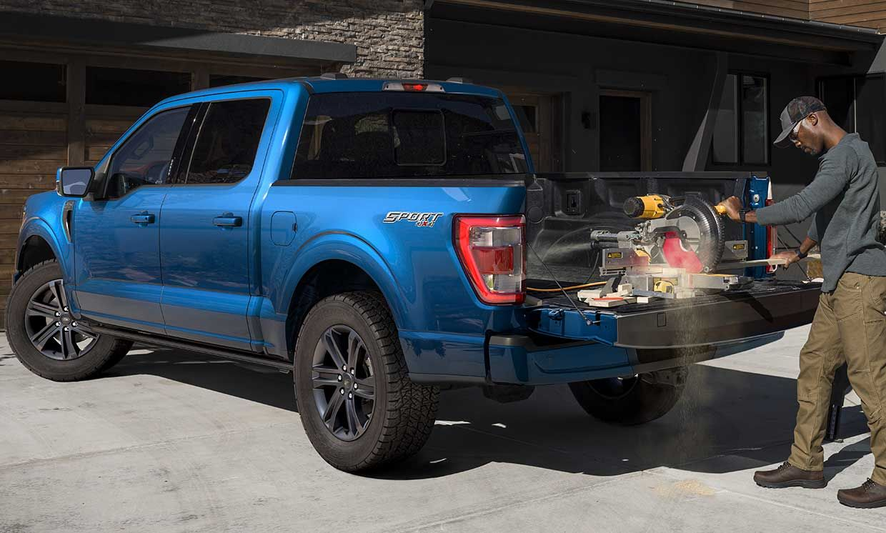 Photograph of a man using a saw plugged into Ford's new Pro Power Onboard mobile generator for its new F-150 pickup.