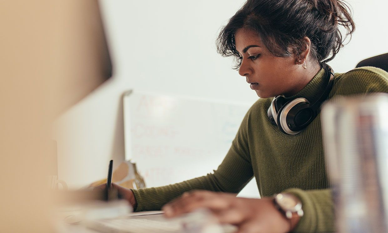 Photograph of a woman working in front of a computer.