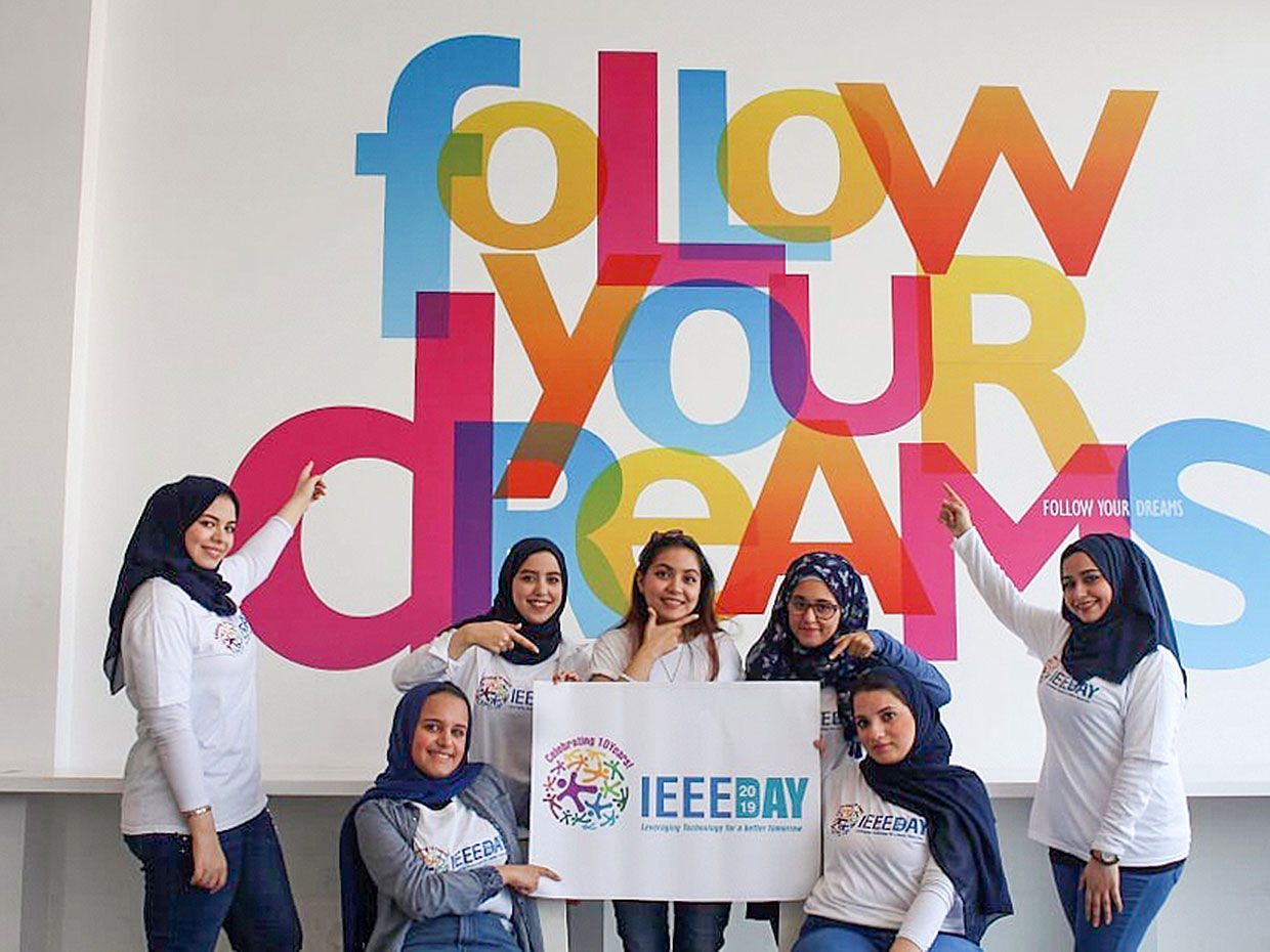 Photograph of members of the Ajman University Student Branch - UAE in front of a sign that says follow your dreams.