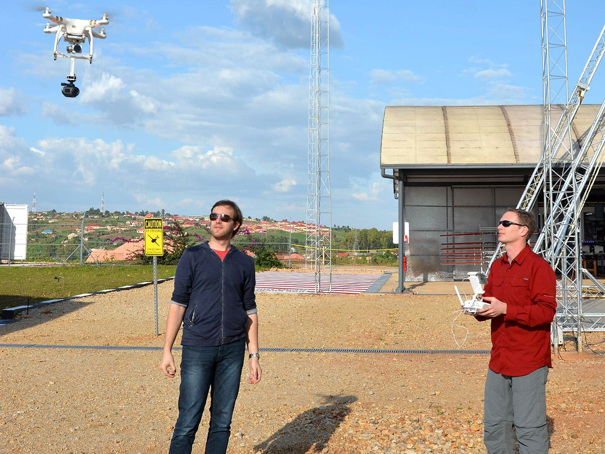 Photograph of Michael Koziol (left) and Evan Ackerman operating a drone in the air above them.