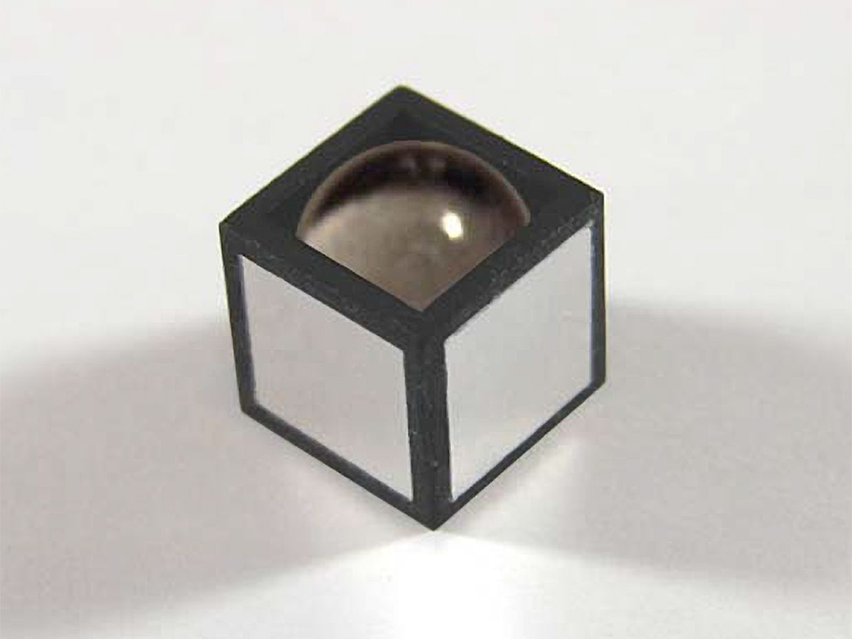 Photograph of the sensor, with the top electrode removed. It looks like a black and white cube with a drop of water bulging from the top. The dimensions are 3 × 3 × 3 mm.