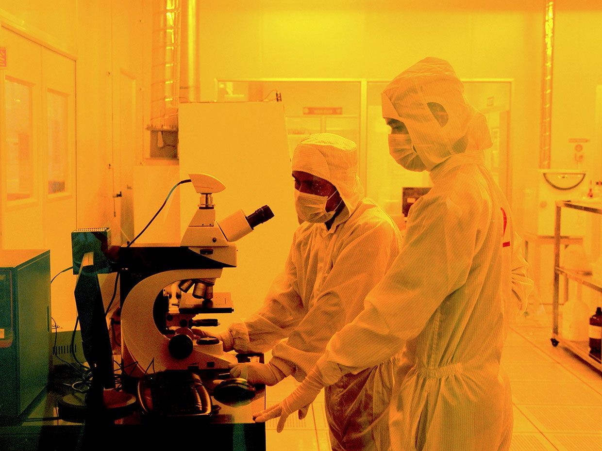 Photograph of two workers wearing bunny suits inside or a semiconductor fabrication lab.