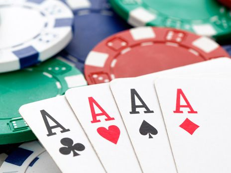 Poker chips and four aces playing cards.