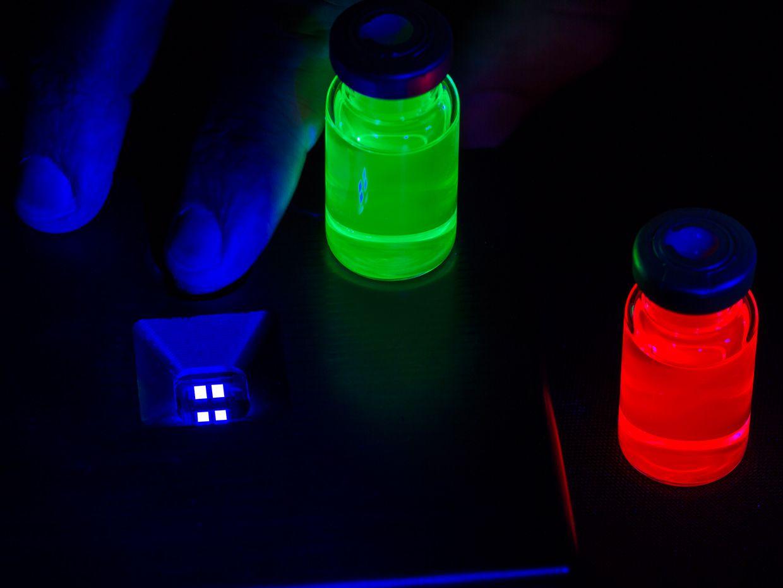 Printed pixels of electroluminescent blue quantum dots alongside vials of red and green quantum dots.