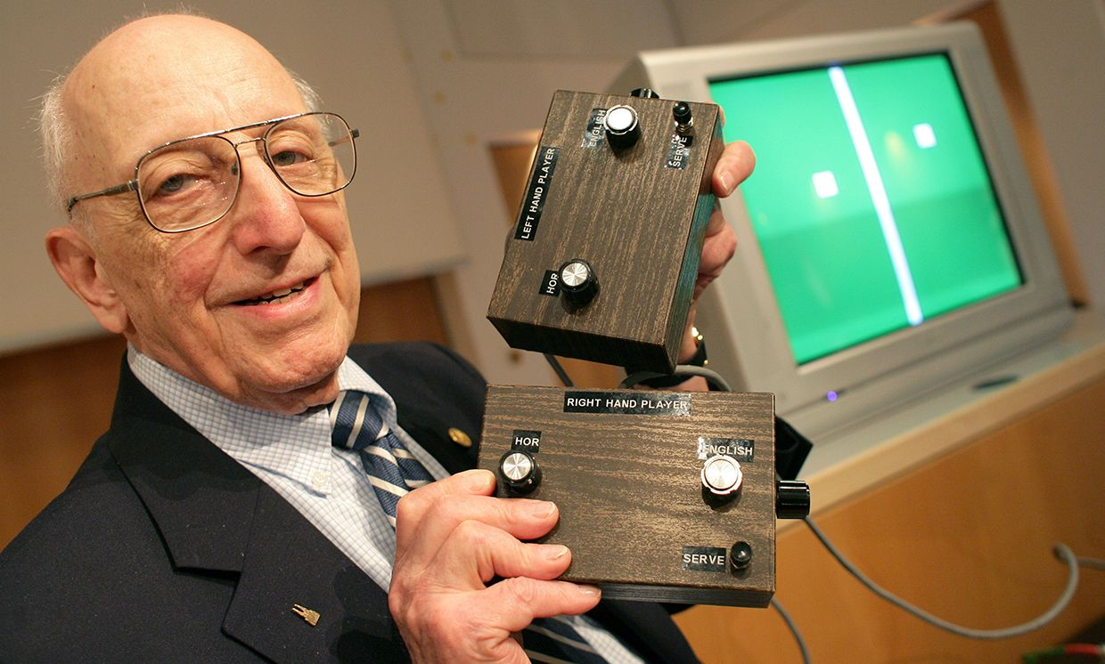 Ralph Baer, a smiling older man in glasses, holds two brown boxes with nobs. In the background a screen displays white shapes on a green background.