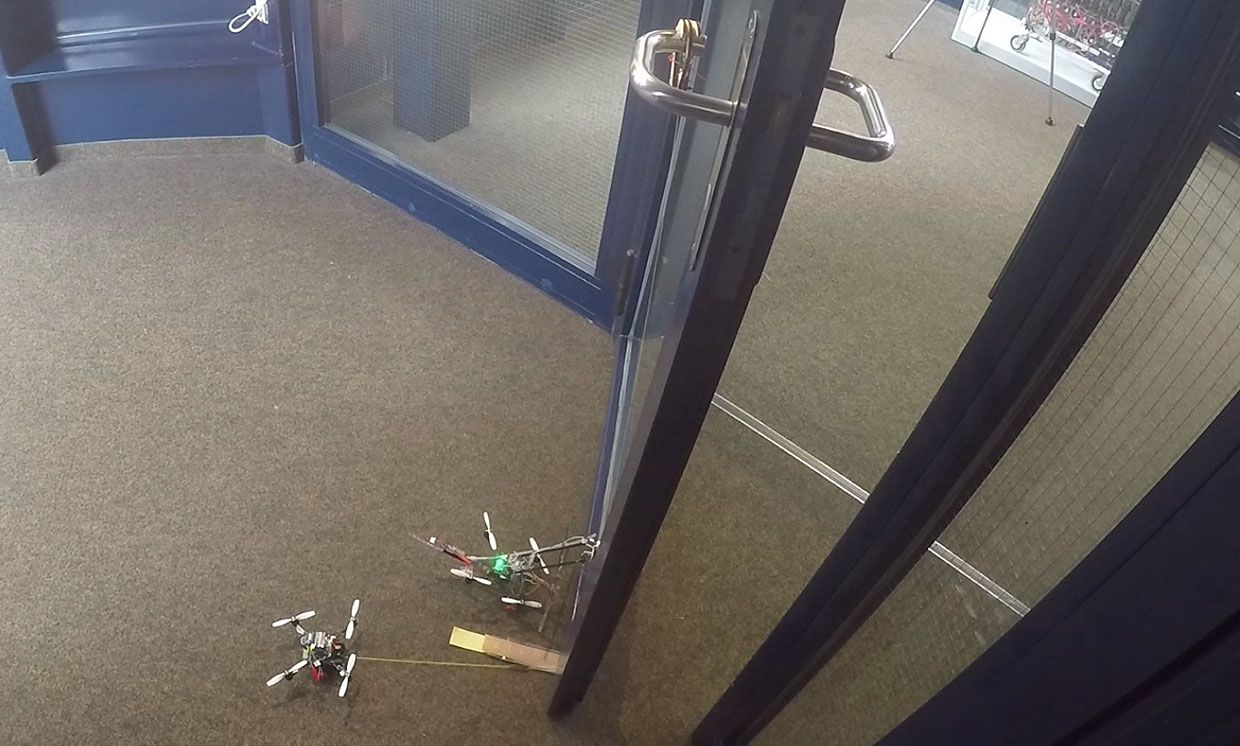 Still image from a video showing the drones collaborating to open a door.